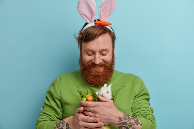 Koncepcja wesołych świąt. brodaty rudy mężczyzna nosi uszy królika, trzyma małego białego króliczka z ozdobionymi kolorowymi jajkami, wiosenne święta religijne celebraes, pozuje na niebieskiej ścianie. polowanie na jajka