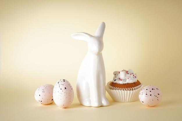 Koncepcja wesołych świąt. ciasto wielkanocne, zajączek i jajka na żółtym tle.