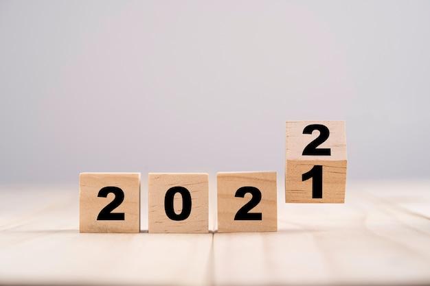 Koncepcja wesołych świąt i szczęśliwego nowego roku, odwracanie drewnianego bloku kostki zmienia się z 2021 na 2022.