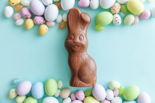 Koncepcja wesołych świąt. przygotowanie do wakacji. wielkanocne cukierki czekoladowe jajka króliczek i żelki słodycze na białym tle na modnym pastelowym niebieskim tle