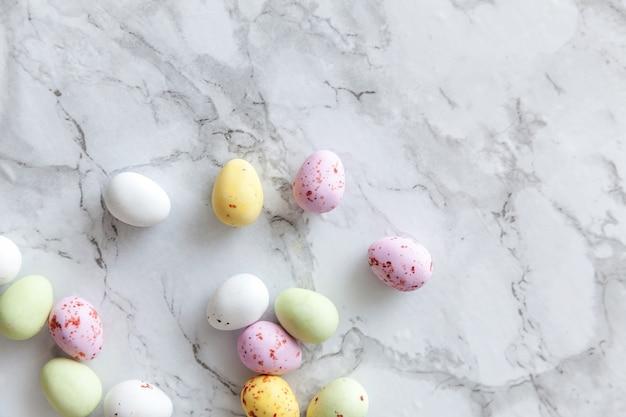 Koncepcja wesołych świąt. przygotowanie do wakacji. wielkanocne pastelowe cukierki czekoladowe jajka słodycze na modnym szarym tle marmuru