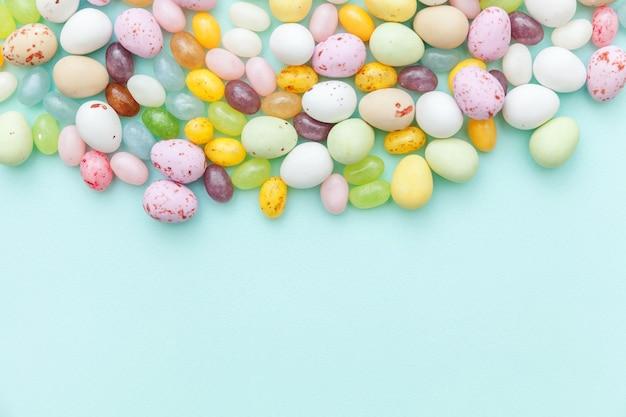 Koncepcja wesołych świąt. wielkanocne cukierki czekoladowe jajka i galaretki na białym tle na modnym pastelowym niebieskim tle