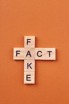 Koncepcja wiadomości i informacji. krzyżówka z fałszywymi słowami i faktem na białym tle na pomarańczowym tle.