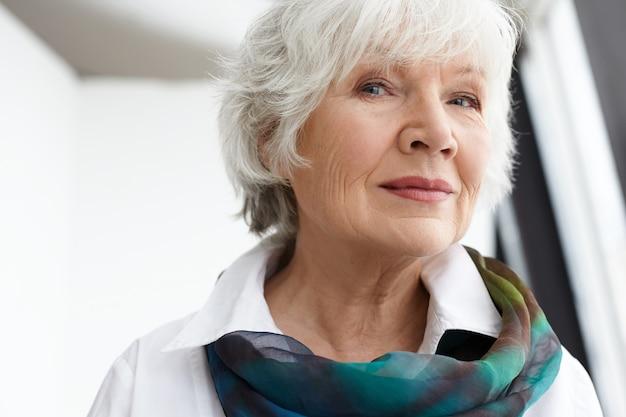 Koncepcja wieku, dojrzałości, urody, stylu i mody. zamknij się obraz eleganckiej stylowej starszej starszej kobiety ze zmarszczkami, siwymi włosami i naturalnym makijażem spędzającym wolny czas w pomieszczeniu, uśmiechając się