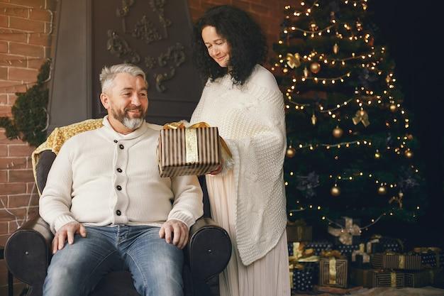 Koncepcja wieku i osób. starszy para z szkatułce na tle świateł. kobieta w białej dzianinowej bluzie.