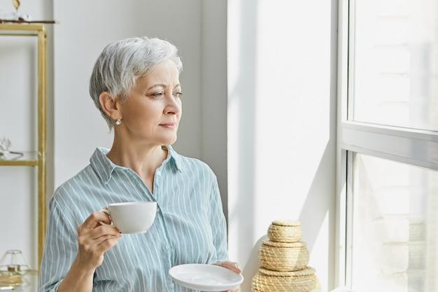 Koncepcja wieku, stylu i dojrzałości. piękna stylowa kobieta w średnim wieku z siwymi włosami pixie pijąca herbatę ziołową, trzymając biały kubek i spodek, patrząc przez okno, z zamyślonym wyrazem twarzy