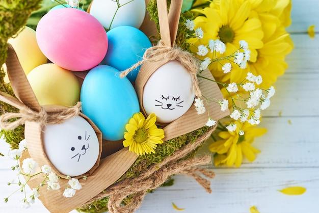 Koncepcja wielkanoc. jaja w koszu ozdobione kwiatami