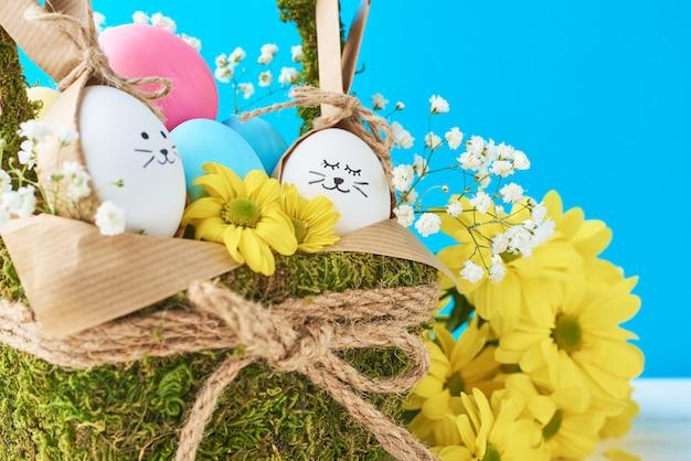 Koncepcja wielkanoc. jajka w koszu dekorującym z kwiatami na błękitnym tle
