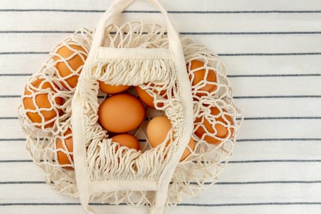 Koncepcja wielkanocna. brak koncepcji plastikowej torby. minimalistyczny styl. beżowa siatkowa torba na zakupy z brązowymi kurzymi jajami na tle włókienniczym.