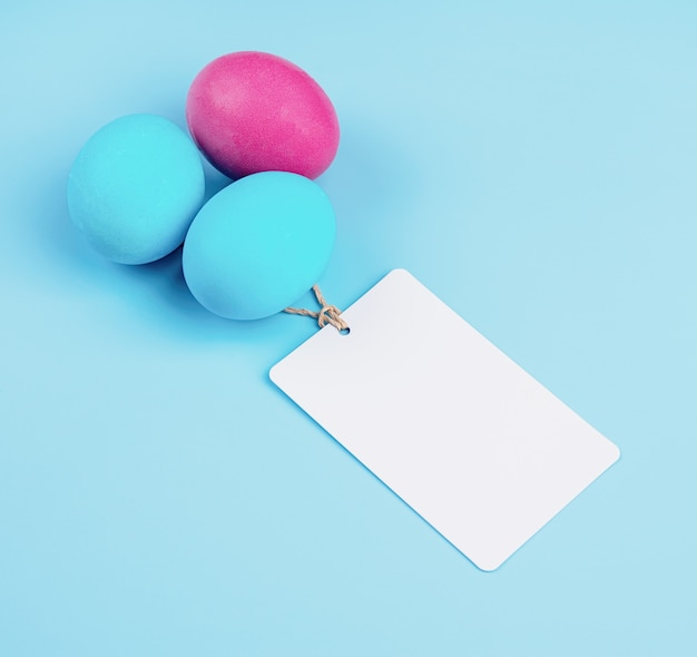 Koncepcja wielkanocna. kolorowe jajka z pustymi tagami na białym tle na niebieskim tle z miejsca na kopię