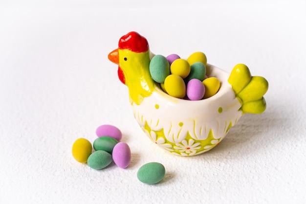 Koncepcja wielkanocna. mini jaja w małej kury talerz na białym tle.