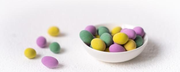 Koncepcja wielkanocna. mini jaja w małym talerzu na białym tle. kolor jaja wzór, tło wielkanoc.