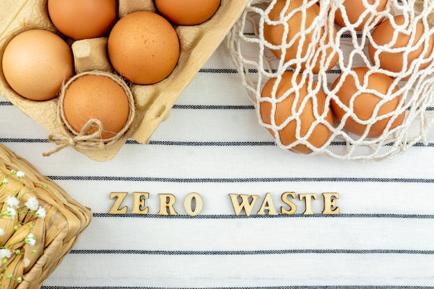 Koncepcja wielkanocna zero waste. brak koncepcji plastikowej torby. minimalistyczny styl. beżowa siatkowa torba na zakupy z brązowymi kurzymi jajami na tle włókienniczym.