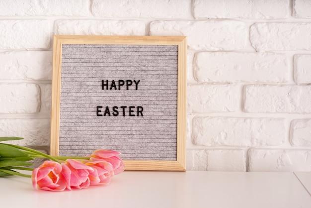 Koncepcja wielkanocnego święta. wazon z tulipanów i szarej filcowej tablicy ze słowami wesołych świąt na tle białej cegły
