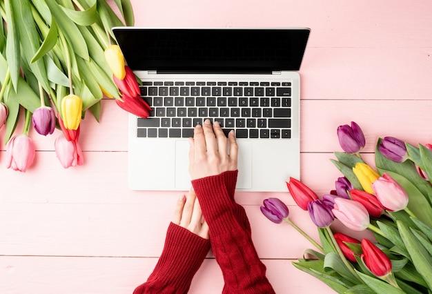 Koncepcja wielkanocy i wiosny. kobieta ręce, wpisując na klawiaturze laptopa. kobieca przestrzeń robocza ozdobiona tulipanami