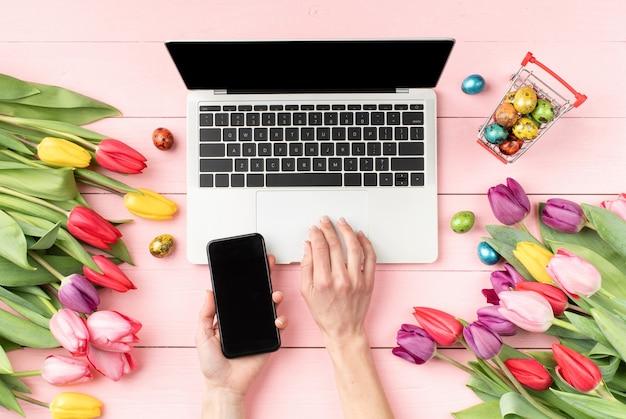 Koncepcja wielkanocy i wiosny. widok z góry kobiecego obszaru roboczego z laptopem, tulipany, jaja i kobiece dłonie przy użyciu telefonu komórkowego na różowym tle