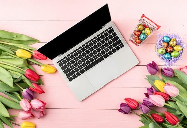 Koncepcja wielkanocy i wiosny. widok z góry laptopa, kolorowe tulipany i pisanki na różowym tle drewnianych