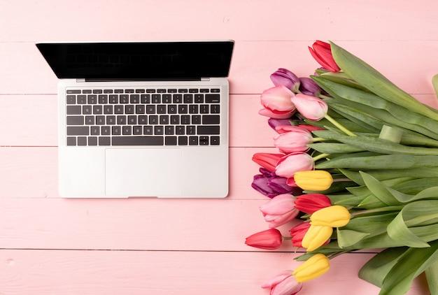 Koncepcja wielkanocy i wiosny. widok z góry laptopa ozdobiony kwiatami tulipanów na różowym tle drewnianych