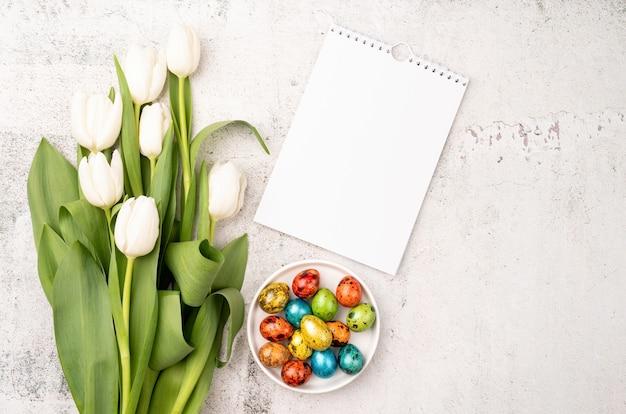 Koncepcja wielkanocy i wiosny. widok z góry na białe tulipany, pusty kalendarz i kolorowe pisanki na betonowym backgrund