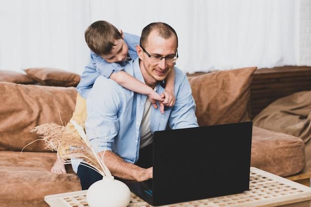 Koncepcja wielozadaniowości, freelance i ojcostwa - pracujący ojciec z chłopcem-dzieckiem i laptopem w biurze domowym