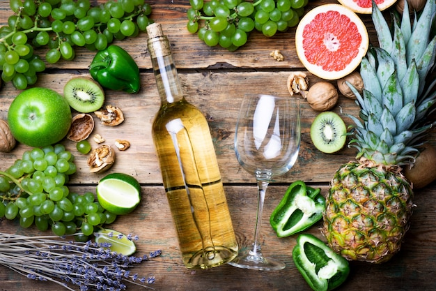 Koncepcja wina. butelka i kieliszek młodego białego wina bio z zielonymi winogronami, grejpfrutem i innymi owocami na starym drewnianym stole