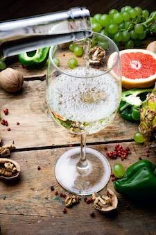 Koncepcja wina. kieliszek młodego białego wina bio z zielonymi winogronami, grejpfrutem i innymi owocami na starym drewnianym stole