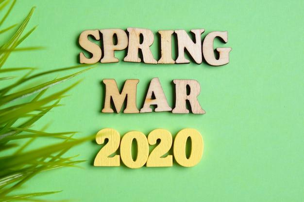 Koncepcja wiosny - marca w nowym roku. drewniane liczby 2020 z literami z liśćmi