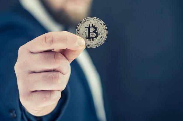 Koncepcja wirtualnej waluty i blockchain. biznesmen w niebieskiej kurtce, trzymając w rękach bitcoin.
