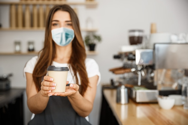 Koncepcja właściciela firmy - piękna kaukaska barista w masce na twarz oferuje jednorazową gorącą kawę w nowoczesnej kawiarni