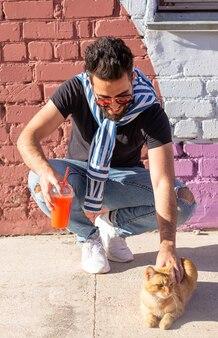 Koncepcja właściciela i przyjaźni - przystojny mężczyzna trzyma i przytula ładny kot imbir. kot z ciekawym wyrazem twarzy.