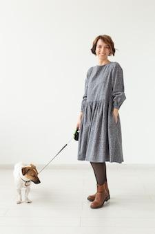 Koncepcja właściciela mody i zwierzaka - młoda kobieta pozuje w ubraniach z jack russell na białej ścianie.