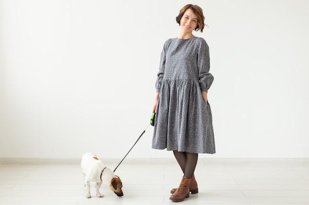 Koncepcja właściciela mody i zwierzaka - młoda kobieta pozuje w ubraniu z jackiem russellem