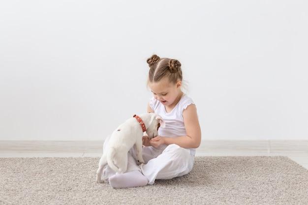 Koncepcja właściciela zwierzaka, dzieci i psy - mała dziewczynka siedzi na podłodze z uroczym szczeniakiem jack russell terrier i bawi się