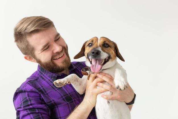 Koncepcja właściciela zwierzaka - młody człowiek bawi się ze szczeniakiem na białej ścianie