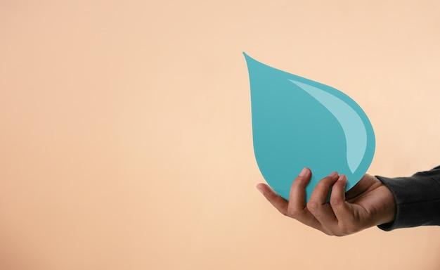 Koncepcja wody na świecie. ręka trzyma papier kropla wody. zrównoważone, bezpieczne i czyste warunki sanitarne, csr. odnawialna zielona energia. odpowiedzialność społeczna lub wkład społeczny firmy