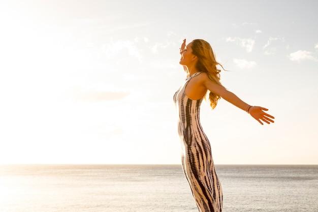 Koncepcja wolności i radości ludzie szczęśliwy styl życia ze stojącą i wesołą piękną młodą kaukaską kobietą otwierającą ramiona i cieszącą się rekreacją na świeżym powietrzu