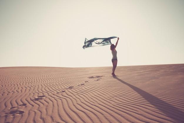 Koncepcja wolności i szczęścia ze stojącą damą na wydmach piaszczystej pustyni, ciesząc się naturą oudoor z czystym białym niebem