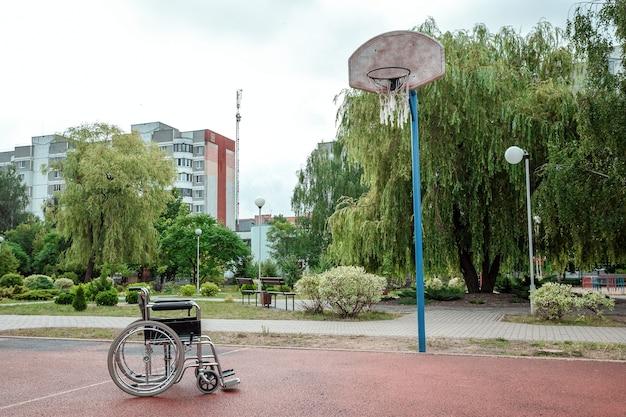 Koncepcja wózka inwalidzkiego na boisku sportowym, osoba niepełnosprawna, szczęśliwe życie, sparaliżowana. wózek inwalidzki na boisku do koszykówki.