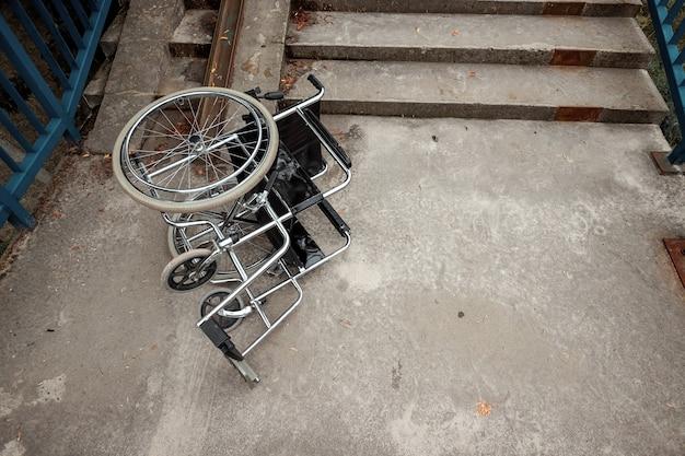 Koncepcja wózka inwalidzkiego na schodach przewrócona, niepełnosprawna, pełna życia, sparaliżowana. problemy osoby niepełnosprawnej.