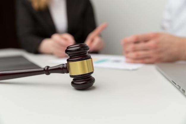 Koncepcja wsparcia prawnego. ludzie siedzący przy biurku z drewnianym młotkiem na nim.