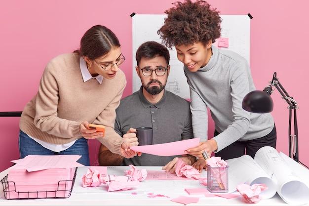 Koncepcja współpracy ludzi i czasu pracy. grupa wykwalifikowanych profesjonalnych współpracowników pozuje przy biurku w biurze, skupiona na szkicu, próbując znaleźć wspólne rozwiązanie, tworząc rysunki architektoniczne.