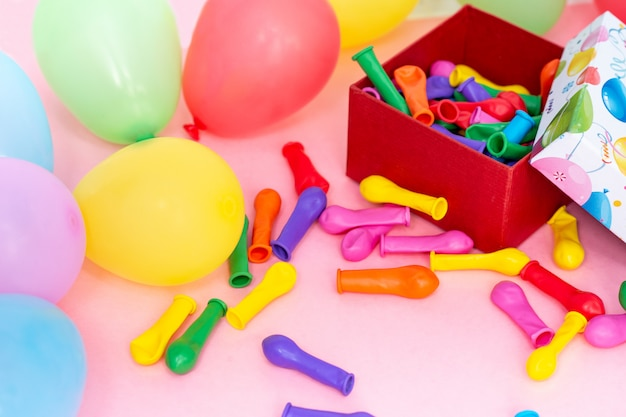 Koncepcja wszystkiego najlepszego. kolorowe balony i pudełko na różowym stole, układ widok z góry
