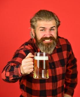 Koncepcja wszystkiego najlepszego. zrób łyk. świętuj z alkoholem. rzemiosło. dojrzały brodaty mężczyzna trzyma szklankę do piwa. wypoczynek i świętowanie. mężczyzna pije piwo w pubie. browar piwny. brutalny hipster pije piwo.