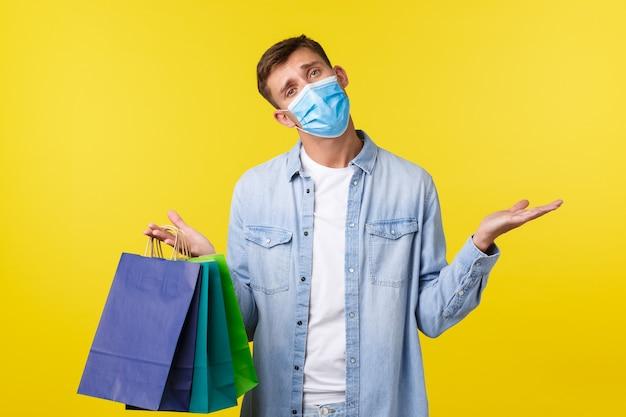 Koncepcja wybuchu pandemii covid-19, zakupów i stylu życia podczas koronawirusa. niezdecydowany, zaintrygowany przystojny facet w masce medycznej, bezradny wzruszający ramionami i niosący torby ze sklepu.