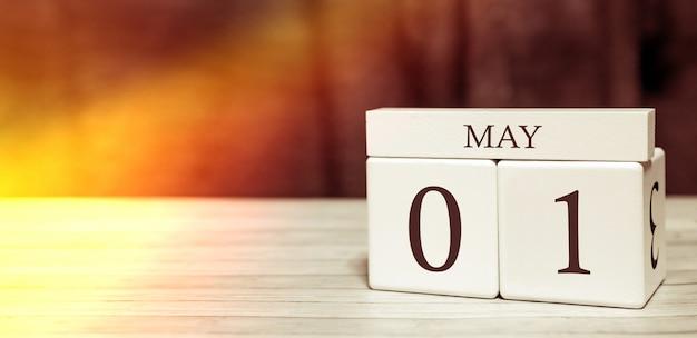 Koncepcja wydarzenia przypomnienia kalendarza. drewniane kostki z liczbami i miesiącem 1 maja