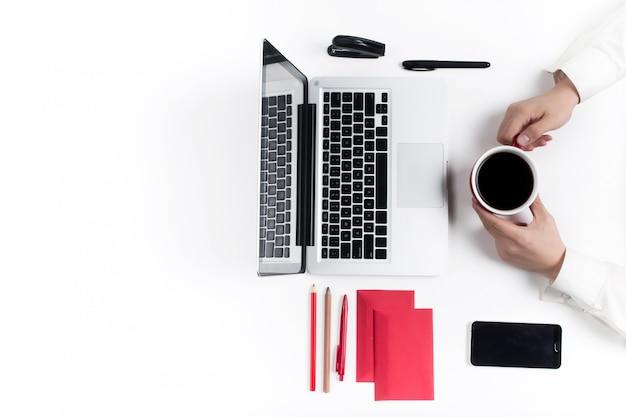 Koncepcja wygodnych miejsc pracy. ręce i gadżety na białym biurku