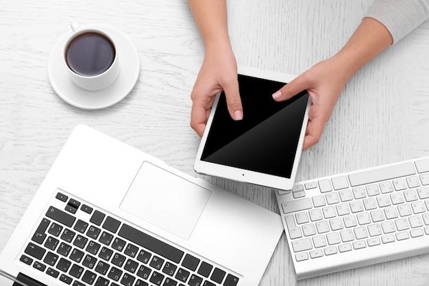 Koncepcja wykorzystania elektroniki. kobieta pracuje w biurze, z bliska. komputer, laptop, tablet, filiżanka kawy i inne rzeczy na stole. widok z góry