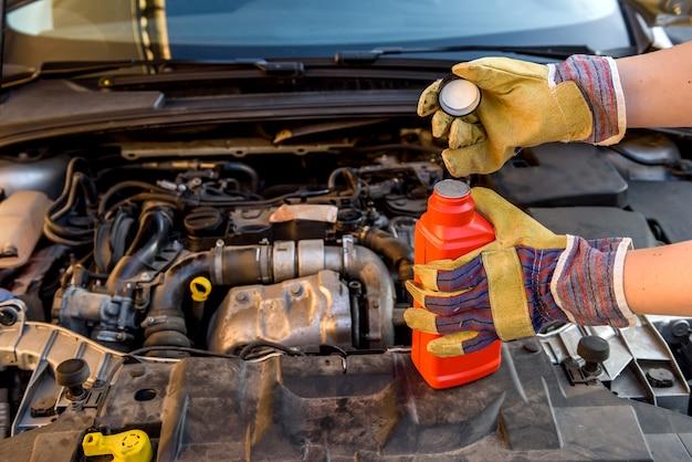 Koncepcja wymiany oleju. mężczyzna ręka w rękawicy z butelką oleju i silnikiem samochodowym z bliska
