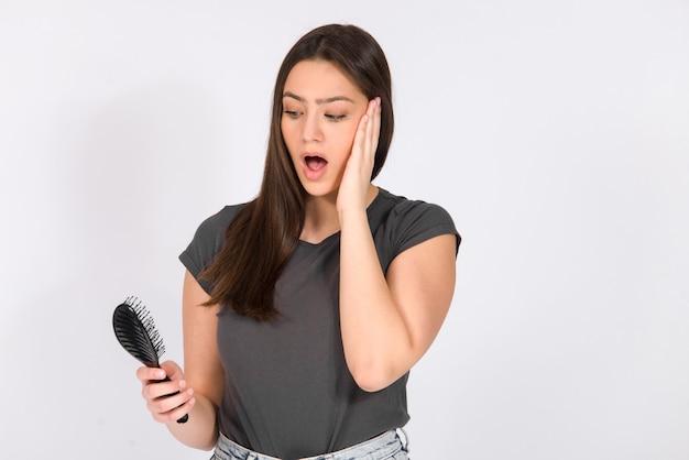 Koncepcja wypadania włosów. dziewczyna trzyma szczotka do włosów z zaskoczony wyraz twarzy, na białym tle