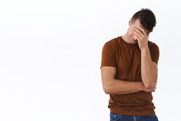 Koncepcja wypalenia emocjonalnego, stresu i ludzi. dorosły mężczyzna w depresji, facepalm, ponury i przygnębiony, zakrywający oczy i wzdychający